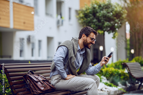 Side view of stylish smiling caucasian businessman sitting on bench in park and using smart phone Wallpaper Mural