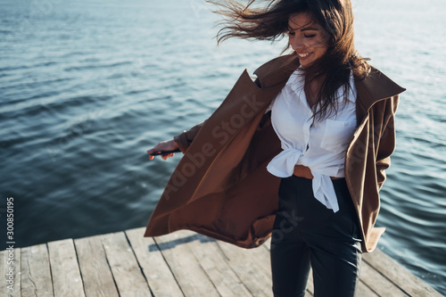 Obraz Beautiful Young Stylish Girl in Coat Walking in the Spring Beach at Sunset - fototapety do salonu