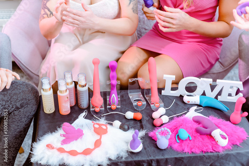 Women discussing various sex toys during adult party Fototapete