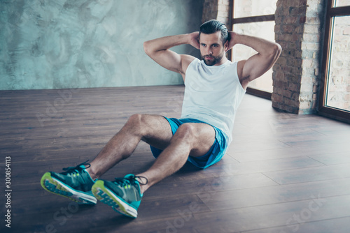 Fotomural Photo of macho sportsman guy doing static sit ups sitting floor determined perso