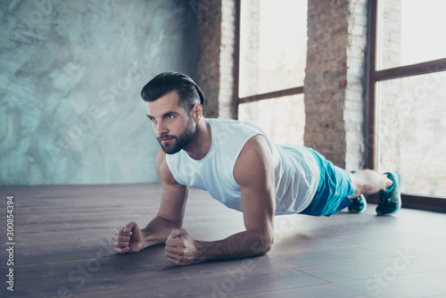 fototapeta na drzwi i meble Profile photo of macho sportsman guy doing plank on elbows hands leaning floor determined sportswear tank-top shorts sneakers training house studio windows indoors