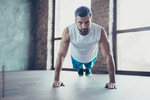 Photo of handsome sportsman trainer guy showing client how to do push ups and plank correctly hands leaning floor sportswear tank-top training house studio windows indoors