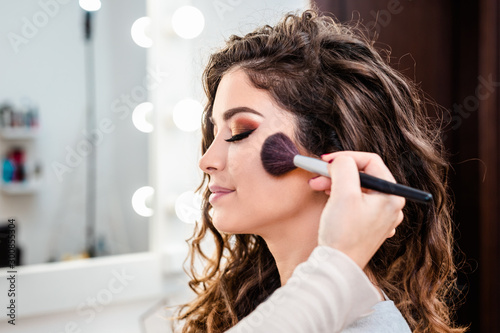 Obraz Make up artist applying professional make up of beautiful young woman. - fototapety do salonu