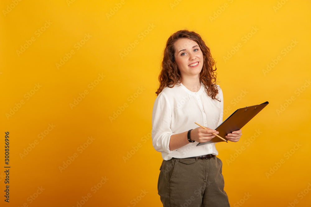 Fototapety, obrazy: Beautiful young girl with a clipboard and a pencil smiles and looks at the camera standing isolated on yellow background.