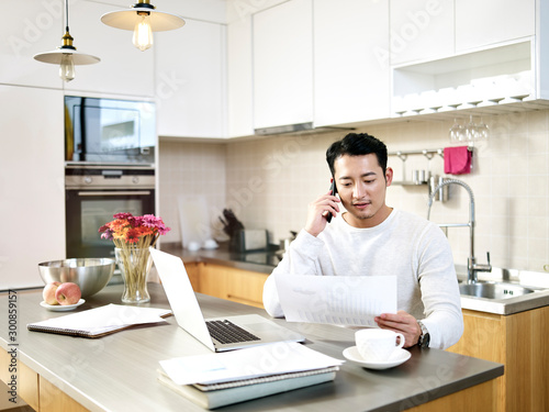 Obraz young asian man working from home - fototapety do salonu
