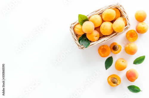 Leinwand Poster Collect apricots, white background top view copy space, pattern with leaves