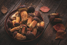 Edible Forest Mushrooms In A Clay Dish On A Wooden Rustic Table
