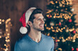 Photo of funky cute cheerful handsome man in santa headwear smiling toothily with bristle lights ornament garland illumination behind him with fir tree