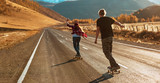 Young couple riding on longboards