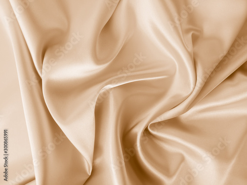 Beautiful smooth elegant wavy beige / light brown satin silk luxury cloth fabric texture, abstract background design. Copy space.