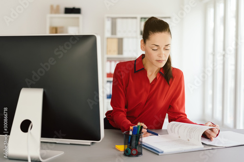 Photo  Young businesswoman concentrating on paperwork