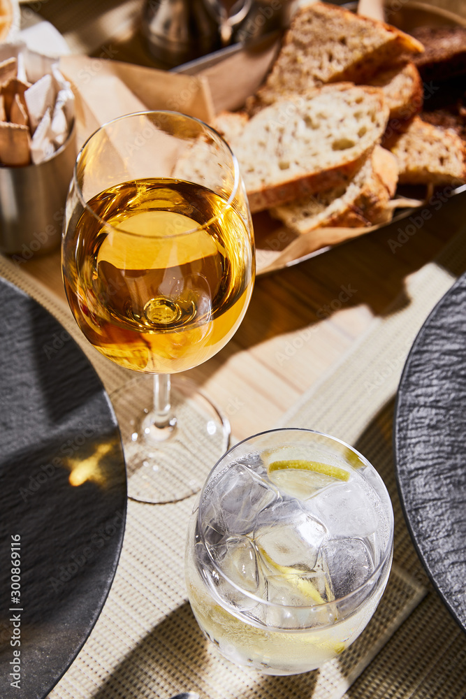 Fototapeta water with ice and lemon near glass of white wine on table in restaurant