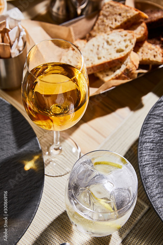 water with ice and lemon near glass of white wine on table in restaurant