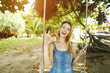 Sunny light photo of young girl riding swing with smartphone on sand and showing ok in Bali.