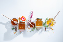 Composition Of Honey  Jars With Honey Sticks ,flowers And Bee Pollen On White Background