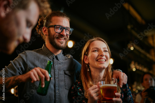 Recess Fitting Alcohol Handsome caucasian man with eyeglasses hugging his girlfriend and talking to her while standing in a pub and drinking beer. Nightlife.