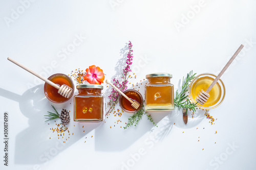 Fotografía Composition of honey  jars with honey sticks ,flowers and bee pollen on white ba