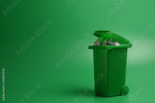 Fototapety, obrazy: Green trash bin on a green background. Ecological concept. Copy space, design