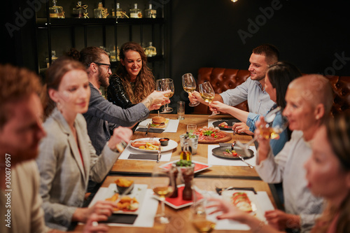 Obraz Group of best friends sitting in restaurant, having dinner, drinking wine and having fun. - fototapety do salonu