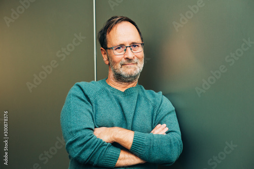 Fotografiet  Outdoor portrait of 50 - 55 year old man wearing green pullover and eyeglasses,