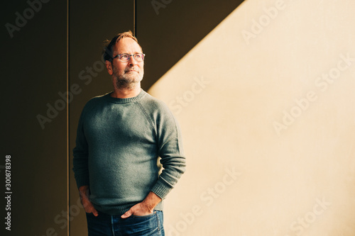 Fotomural  Outdoor portrait of 50 - 55 year old man wearing green pullover and eyeglasses,