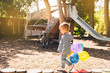 Funny kid girl playing with colorful balloons on playground