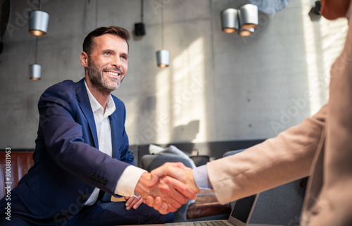 Obraz Business people shaking hands during meeting in cafe - fototapety do salonu
