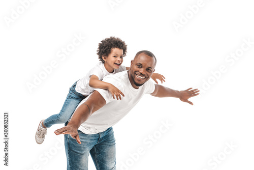 happy african american man piggybacking adorable son and imitating flying on whi Canvas Print
