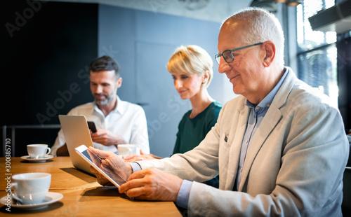 Fotomural  Businessman using digital tablet during meeting in cafe