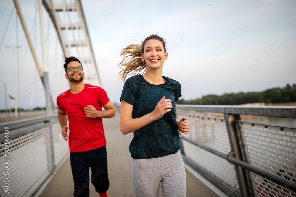 Fototapeta Fitness, sport, people, exercising and lifestyle concept. Couple running outdoor