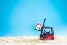 Selective Focus Of Miniature Home Passenger By Forklift Machine On Sand Beach ,image For Real Estate Investment Vacation Concept.