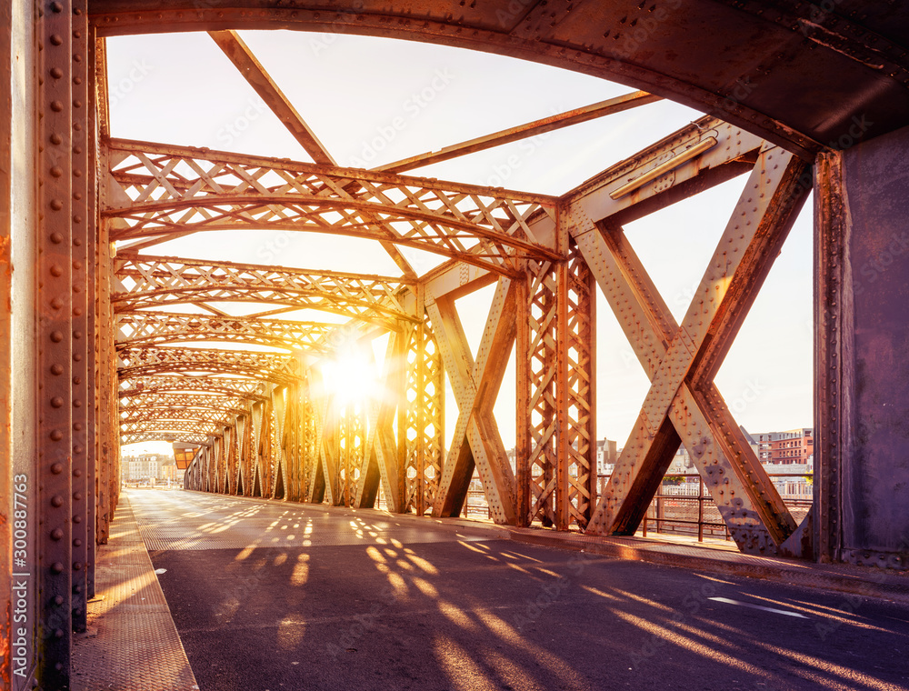 Fototapeta Asphalt road under the steel construction of a bridge in the city on a sunny day. Evening urban scene with the sunbeam in the tunnel. City life, transport and traffic concept.