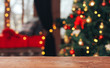 Christmas abstract background. Empty wooden table, horizontal surface in front of Xmas tree. New Year, light bokeh, celebration, holiday, party, copy space