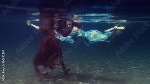 Obraz Two girls in dresses play underwater - fototapety do salonu