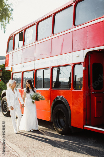 Full view of a happy lesbian couple near the red double decker bus Tablou Canvas