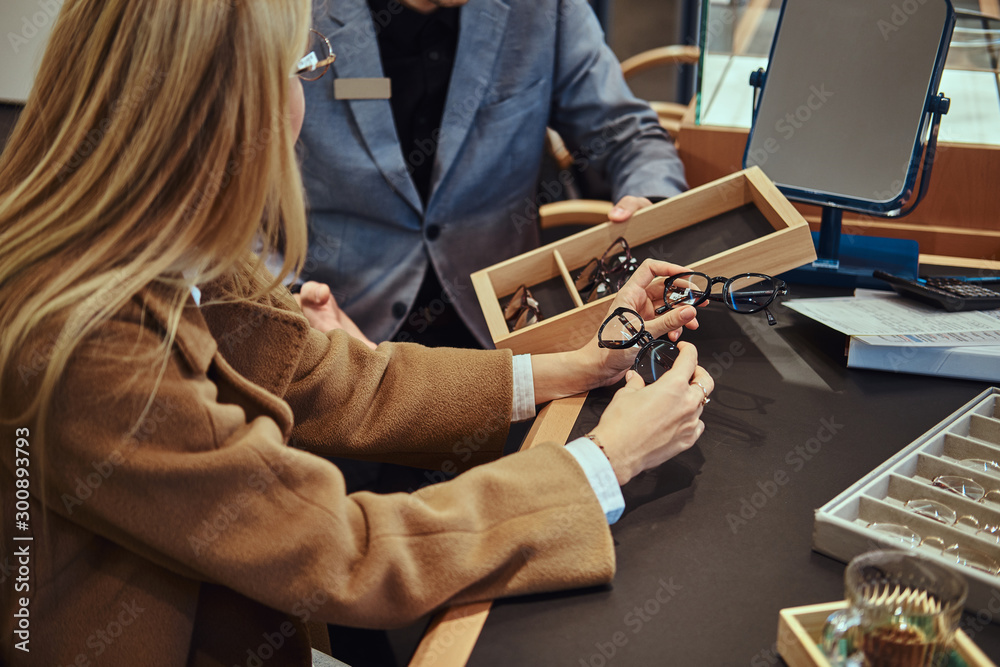 Fototapety, obrazy: Blonde woman is choosing new pair of glasses while shop assistant is showing her variety of glasses.