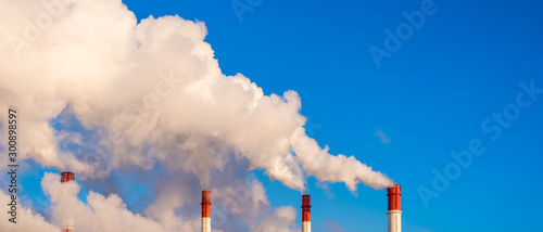 Fotografía  Pipes of a thermal station with clubs of white steam against a blue sky - global
