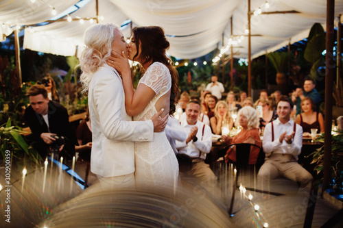 Fotografía  Lesbian couple is kissing in front of guests on the wedding ceremony at the terr