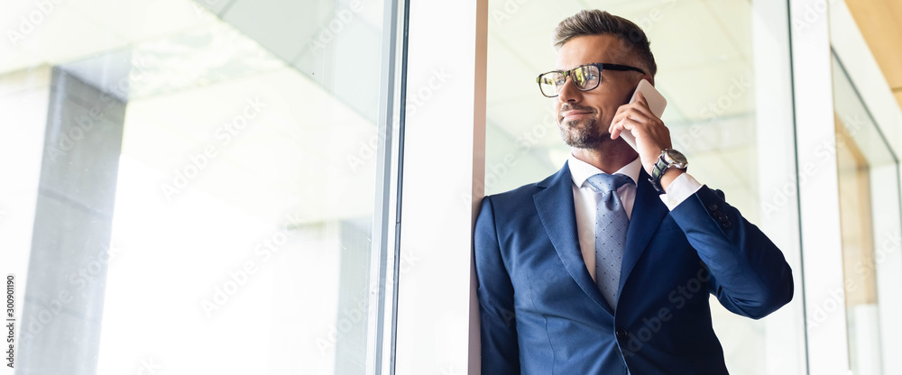 Fototapeta panoramic shot of handsome businessman in suit and glasses talking on smartphone
