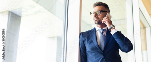 Fotomural  panoramic shot of handsome businessman in suit and glasses talking on smartphone