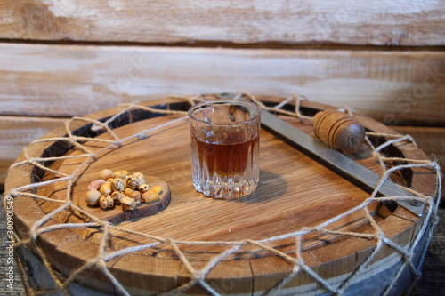 Valokuva shot glass of hooch, nuts and corg  on wooden cask top