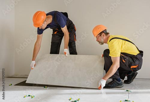 Foto Installing a large ceramic tile.