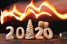 New Year 2020 Concept With Wooden Figures Christmas Tree And Champagne Cork On Black Background With Burning Fire