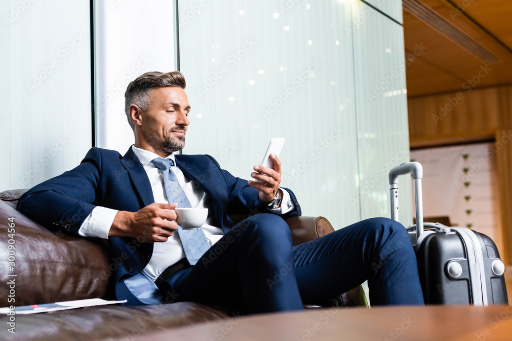 Fototapety, obrazy: handsome businessman in suit using smartphone and holding cup
