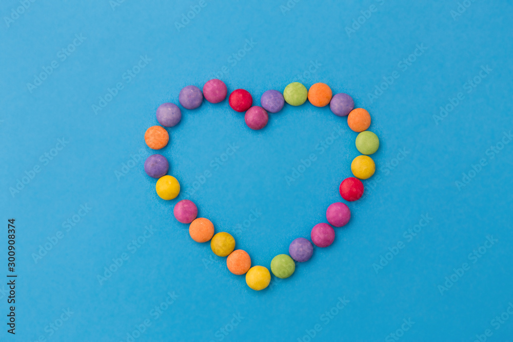 Fototapeta sweets, confectionery and valentine's day concept - bright multicolored candy drops in shape of heart on blue background
