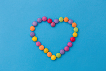 sweets, confectionery and valentine's day concept - bright multicolored candy drops in shape of heart on blue background