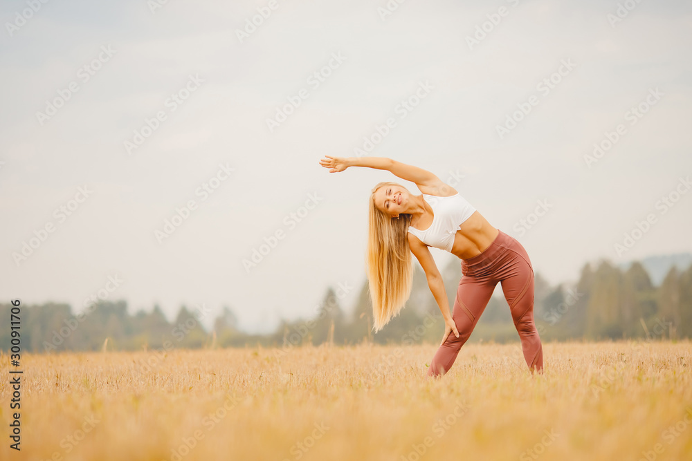 Fototapety, obrazy: Beautiful blonde girl in white T-shirt is stretching in park field, yoga concept