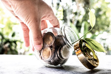 Hand And Glass Jar Piggy Bank With Coins. Plan Your Savings, Run A Growing Business For Success And Save For Retirement