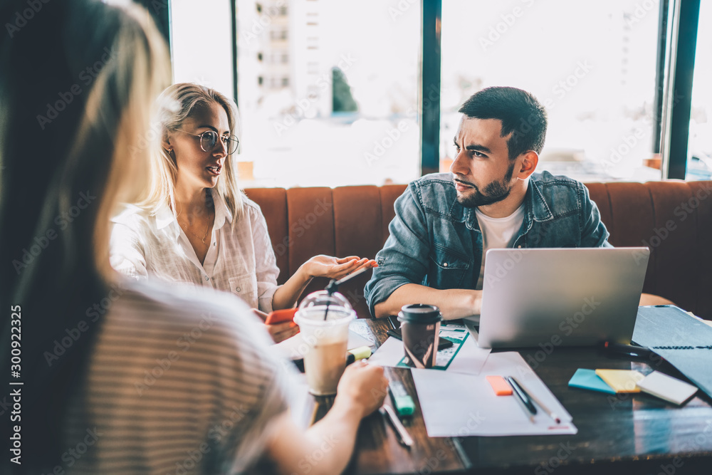 Fototapeta Talking coworkers with studies in cafe