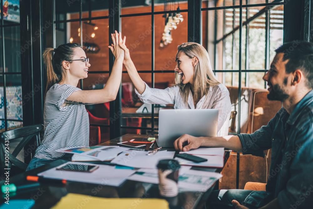 Fototapeta Happy women giving high five coworking in cafe